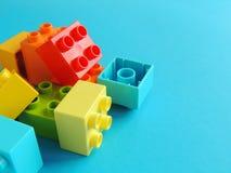 Os tijolos plásticos, blocos brincam no fundo azul brilhante Fotografia de Stock Royalty Free