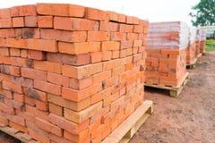 Os tijolos são empilhados em páletes de madeira e preparados para a venda O tijolo da argila é um material de construção ecológic fotografia de stock