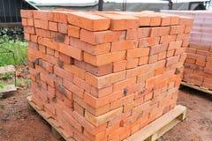 Os tijolos são empilhados em páletes de madeira e preparados para a venda O tijolo da argila é um material de construção ecológic fotografia de stock royalty free