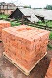 Os tijolos são empilhados em páletes de madeira e preparados para a venda O tijolo da argila é um material de construção ecológic imagens de stock royalty free