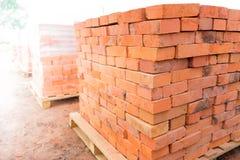 Os tijolos são empilhados em páletes de madeira e preparados para a venda O tijolo da argila é um material de construção ecológic imagens de stock