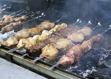 Os tipos diferentes da carne roasted em espetos em carvões durante uma feira da rua fotos de stock