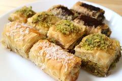 Os tipos diferentes de pastelarias mouthwatering do Baklava serviram na placa branca, foco seletivo e borraram o fundo fotos de stock royalty free