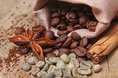 Os tipos diferentes do close-up de feijões de café em um saco, em um café verde, em umas varas da canela e em um anis star, macro Foto de Stock