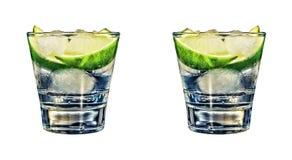 Os tiros do tequila do ouro com cal cortam em seguido isolado no branco Imagens de Stock