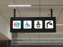 Os toaletes assinam e bebem os painéis da água no aeroporto Imagens de Stock