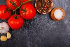 Os tomates brilhantes maduros, apetitosos com grãos de pimenta, o alho e o sal em um fundo preto, lá são sala para o texto Vista imagens de stock