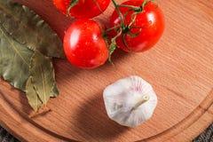 Os tomates com água deixam cair o alho e as folhas de louro Imagens de Stock Royalty Free