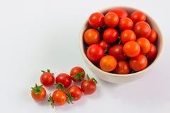 Os tomates de cereja estão em um copo em um fundo branco Foto de Stock