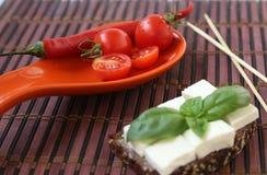 Os tomates de cereja frescos frescos dos tomates de cereja esverdeiam basílica e queijo no brinde Fotografia de Stock Royalty Free