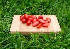 Os tomates de cereja frescos na placa de corte de madeira velha, alimento do close up, dispararam fora Imagem de Stock