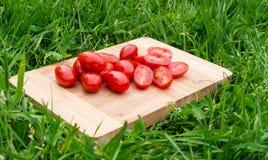 Os tomates de cereja frescos na placa de corte de madeira velha, alimento do close up, dispararam fora Fotos de Stock