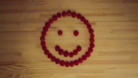 Os tomates de cereja que formam as caras de uma emoção na superfície de madeira, fundo da colheita - pare a animação do movimento video estoque