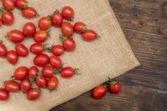 Os tomates de cereja, são tomates pequenos na parte superior de madeira, têm beta-carot fotos de stock