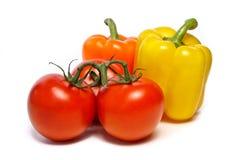 Os tomates e duas pimentas fotos de stock