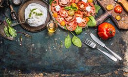 Os tomates e a salada da mussarela, preparação na obscuridade envelheceram o fundo rústico, vista superior Almoço italiano Imagem de Stock Royalty Free