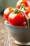 Os tomates em uma bacia no vertical de madeira velho da tabela dobraram Foto de Stock Royalty Free