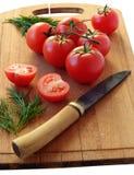 Os tomates inteiros e um cortaram em uma placa de corte Imagem de Stock