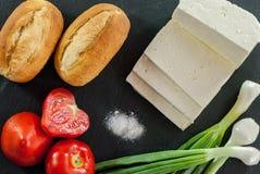 Os tomates maduros vermelhos do queijo de cabra panam bolos e a cebola nova com sal no petisco tradicional da ardósia preta Fotografia de Stock