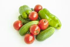 Os tomates, os pepinos e a pimenta dos vegetais esverdeiam em um fundo branco Imagem de Stock Royalty Free