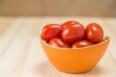 Os tomates postos de conserva em uma bacia de salada na tabela do pinho embarcam Fotos de Stock