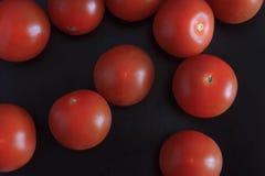 Os tomates vermelhos frescos fecham-se acima no fundo preto fotografia de stock royalty free