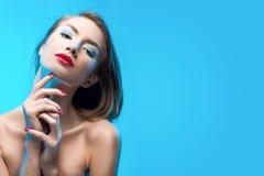 Os toques de sorriso da menina dos bordos vermelhos louros bonitos pelo fá dos dedos Fotografia de Stock Royalty Free