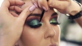 Os toques finais do trabalho do visagist para terminar os olhos verdes compensam por uma mulher gourgeous Sombras do brilho filme