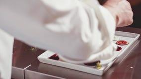 Os toques finais pelo cozinheiro chefe em uma cozinha do restaurante pronta para o serviço filme