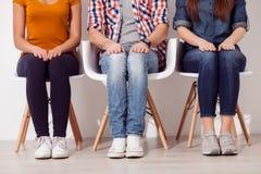 Os três amigos bonitos estão tendo um assento Fotografia de Stock Royalty Free