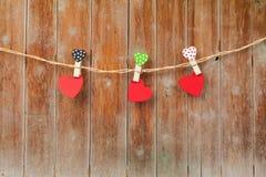 Os três corações de madeira feitos a mão que penduram no pano alinham Fotografia de Stock Royalty Free