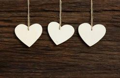 Os três corações do Valentim branco do amor que penduram em vagabundos de madeira da textura Imagens de Stock