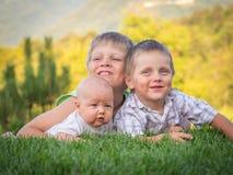 Os três irmãos estão encontrando-se em um gramado verde fotos de stock royalty free
