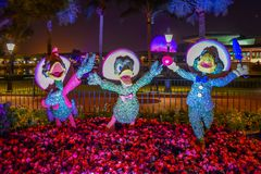 Os tr?s topiaries dos Caballeros Jose Carioca, do Donald Duck e do Panchito Pistoles no cen?rio colorido em Epcot em Walt Disney  foto de stock