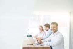 Os três trabalhadores alegres estão usando a tecnologia moderna Foto de Stock Royalty Free