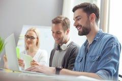 Os três trabalhadores de escritório bonitos estão cooperando com a alegria Imagens de Stock