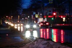 Os traços de faróis do carro na noite refletiram no asfalto chuvoso molhado fotografia de stock