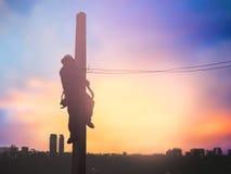 Os trabalhadores bondes da silhueta estão instalando o sistema de alta tensão Fotografia de Stock