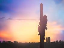 Os trabalhadores bondes da silhueta estão instalando o sistema de alta tensão Fotos de Stock