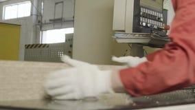 Os trabalhadores caucasianos na roupa suja levam as pranchas de madeira põem-no na pilha na serração vídeos de arquivo
