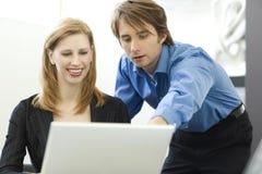 Os trabalhadores compartilham de um computador Fotografia de Stock