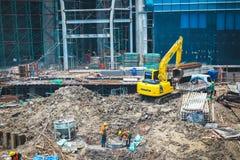 Os trabalhadores da construção com carga e a escavação estão trabalhando imagens de stock