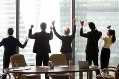 Os trabalhadores de escritório entusiasmado estão o celebratin de aumentação das mãos da janela próxima imagens de stock royalty free