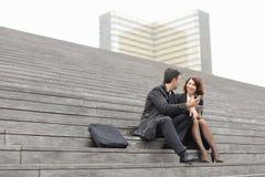 os trabalhadores de escritório masculinos e fêmeas gastam a ruptura que senta-se na escada imagens de stock royalty free