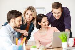 Os trabalhadores de escritório novos alegres estão discutindo um projeto Fotos de Stock Royalty Free