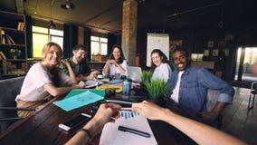 Os trabalhadores de escritório são de sorriso e de riso olhando a câmera durante a instrução com o CEO que senta-se na mesa no es video estoque