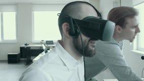Os trabalhadores de escritório usam vidros da realidade virtual no trabalho Close-up de um homem novo calvo em vidros virtuais no filme