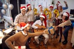 Os trabalhadores de sorriso do negócio têm o divertimento no chapéu de Santa em presentes da festa de Natal e da troca imagem de stock royalty free