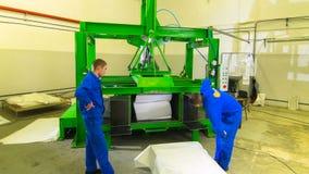 Os trabalhadores de Timelapse puseram o grande cubo da borracha de espuma na máquina da imprensa filme