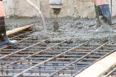 Os trabalhadores derramam a fundação para a construção de uma construção residencial fotos de stock royalty free